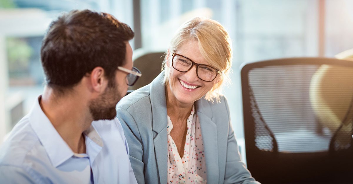 Smiling woman sitting with colleague using educational leadership skills in the workplace