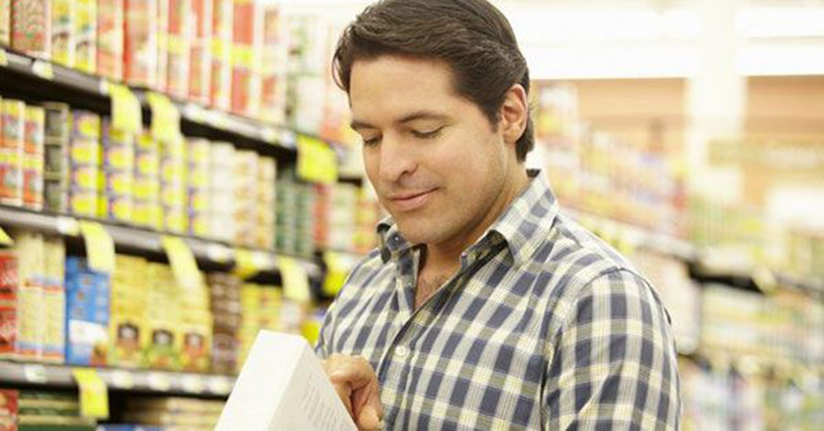 Man reading nutrition label on food product