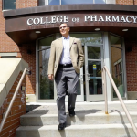 Dan Mickool stepping out of the College of Pharmacy building