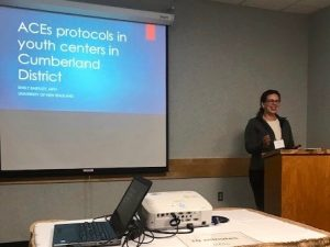 Public health student at MPHA conference at a dais in front of a projected slide that says Adverse Childhood Experiences Protocols in Youth Centers in Cumberland District