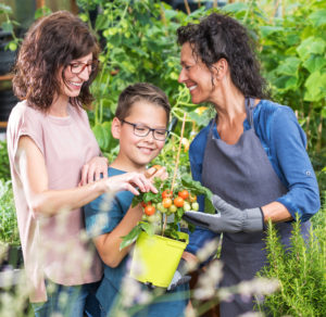 Two women and a boy in a garden looking at fresh vegetables and explaining what the term dietitian means