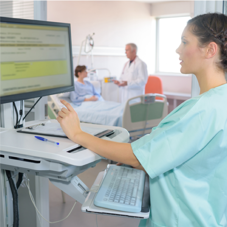 A nurse uses health information technology while a doctor and patient discuss benefits in the background