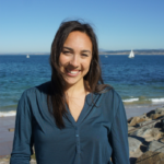 Monica Huelga, who completed her Master of Public Health practicum presentation on environmental health literacy, stands in front of the Pacific ocean with a sailboat in the background
