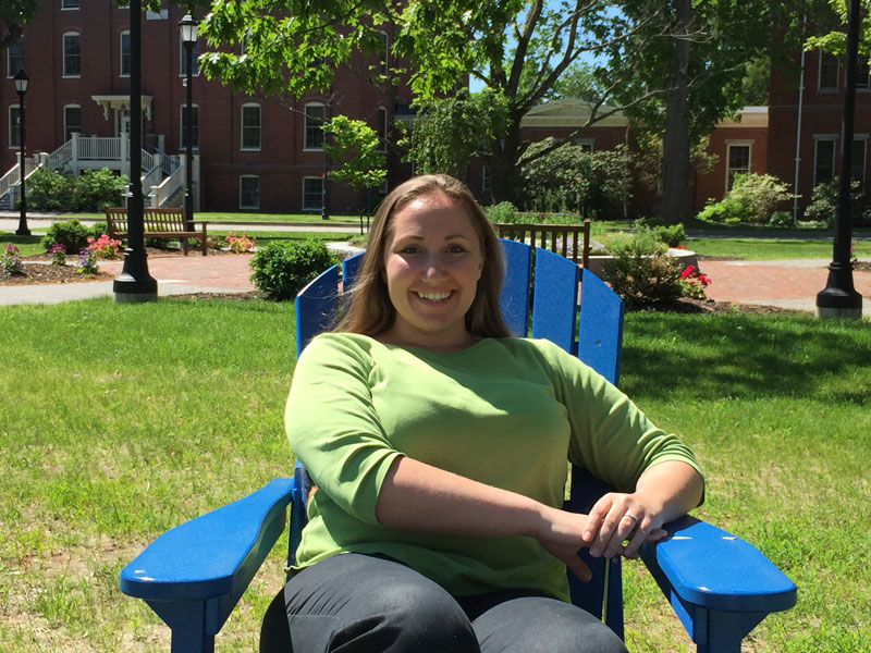 Courtney Mejia, Student Service Advisor for our online science prerequisites, sits in a blue chair on the UNE Portland campus lawn