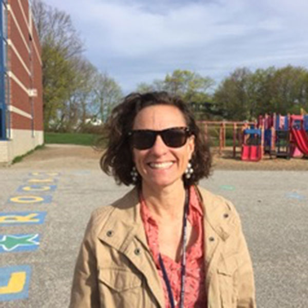 Rachael Flaxman in front of a playground, celebrating Teacher Appreciation Week