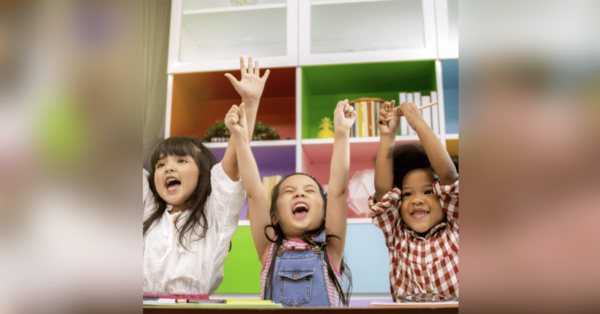 Three girl students throw their hands up in excitement because their teacher used school data analysis