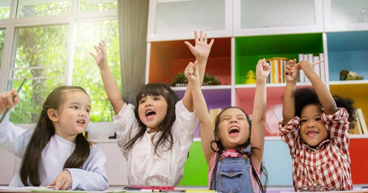 four students raising hands