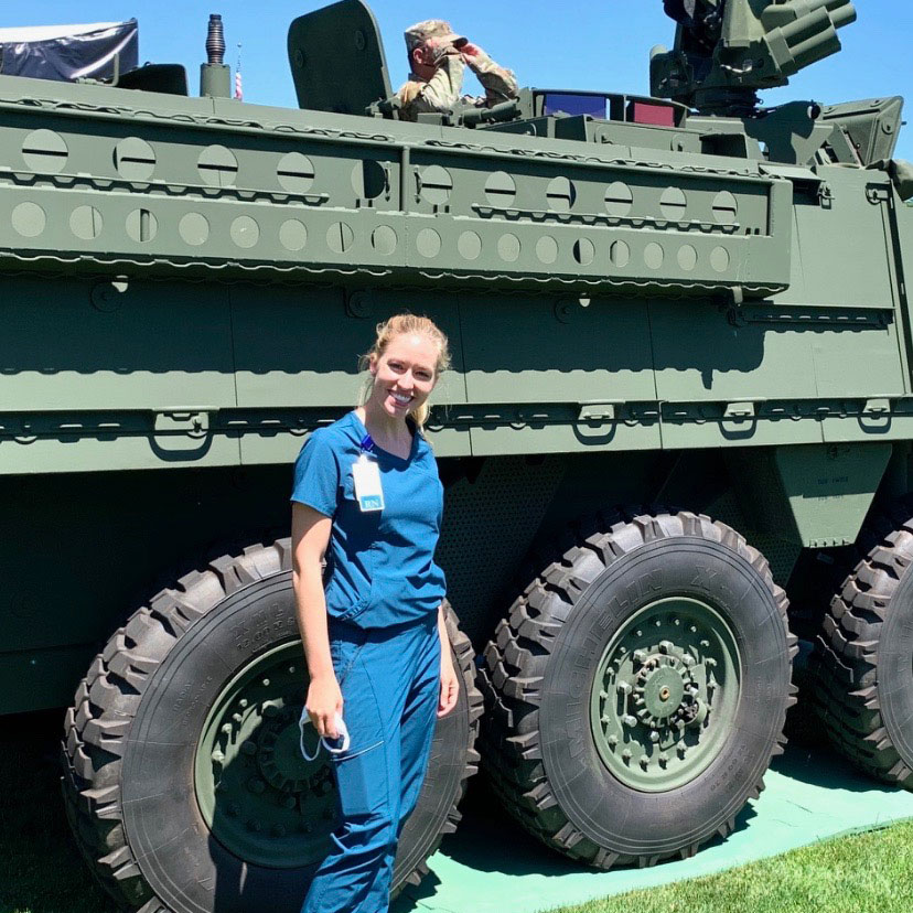 Sarah Kilgore in front of a visiting ICV Stryker, mandatory mask in hand.